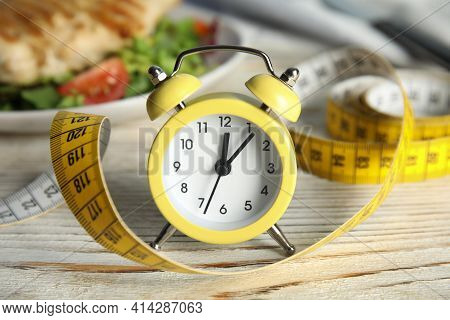 Alarm Clock And Measuring Tape On White Wooden Table. Diet Regime
