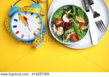 Plate Of Tasty Salad, Alarm Clock And Measuring Tape On Yellow Background, Flat Lay With Space For T