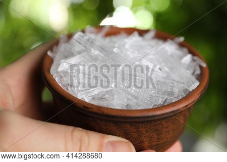 Woman Holding Bowl With Menthol Crystals Against Blurred Background, Closeup