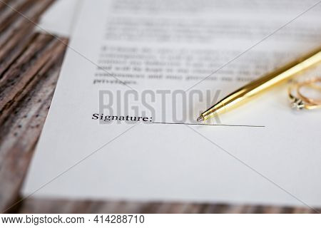 Marriage Contract With Two Golden Wedding Rings And Gold Pen, Prenuptial Agreement, Macro Close Up,