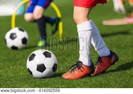 Closeup Of Child Soccer Player Legs Kicking Ball. Kid Running Classic Black And White Football Ball.