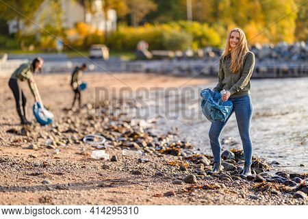 Dedicated Volunteer Team Cleaning Beach For Plastic On Sunny Day