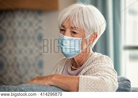 Sad old woman alone wearing protective face mask while sitting at home during Covid-19 quarantine. Depressed elder suffering from loneliness during lockdown due to covid in a care centre.