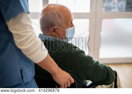 Depressed senior patient sitting on wheelchair and wearing protective face mask during covid-19 pandemic. Nurse assisting sad elderly man using wheelchair wearing surgical face mask.