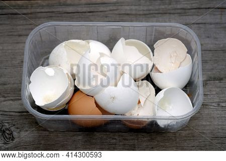 Eggshells In A Plastic Container On A Wooden Background. Collection Of Eggshells Closeup.