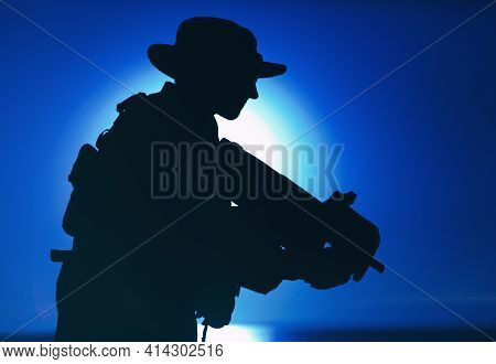 Silhouette Of Army Special Forces Commando, Soldier In Boonie Hat Aiming And Shooting Bullpup Submac
