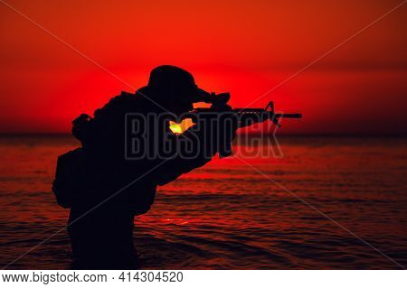 Silhouette Of Army Soldier Aiming And Shooting Service Rifle While Standing Knee-deep In Sea Water.