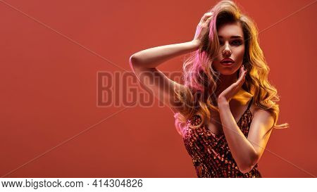Portrait of beautiful young woman with bright shiny makeup. Blonde with brightly colored long hair. Pretty girl with long curly hair.   Fashion model in a shiny dress posing at studio.