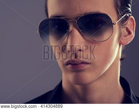 Handsome fifteen years old guy in a black stylish sunglasses. Face of a beautiful teenage boy close-up. Portrait of a  confident young caucasian man. Male model posing at studio. Low key style.