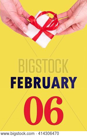 February 6th. Festive Vertical Calendar With Hands Holding White Gift Box With Red Ribbon And Calend