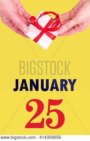 January 25th. Festive Vertical Calendar With Hands Holding White Gift Box With Red Ribbon And Calend