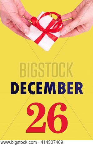 December 26th. Festive Vertical Calendar With Hands Holding White Gift Box With Red Ribbon And Calen