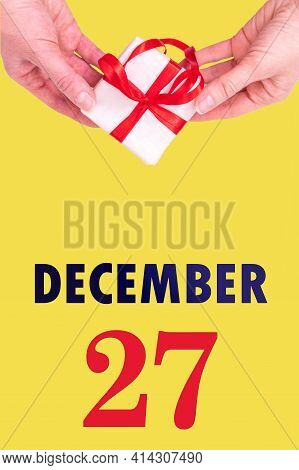 December 27th. Festive Vertical Calendar With Hands Holding White Gift Box With Red Ribbon And Calen