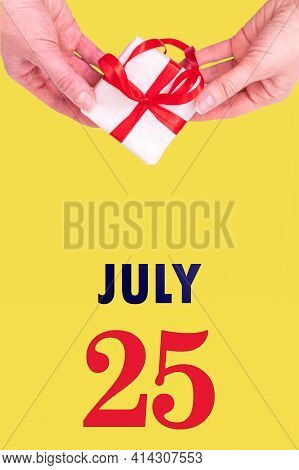 July 25th. Festive Vertical Calendar With Hands Holding White Gift Box With Red Ribbon And Calendar