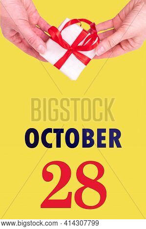 October 28th. Festive Vertical Calendar With Hands Holding White Gift Box With Red Ribbon And Calend