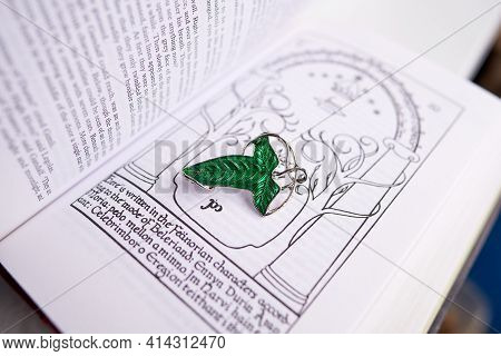 Astrakhan, Russia - 03.26.2021: Green Brooch On Lord Of The Rings Book. The Leaves Of Lorien Were Br