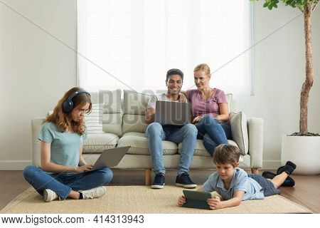 Work From Home. A Parent Using A Laptop On The Couch In The Living Room. Children Use The Phone App,