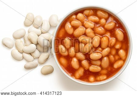 Baked Beans In Tomato Sauce In A White Ceramic Bowl Next To Uncooked Haricot Beans Isolated On White
