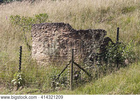 Broken Stone Structure In Long Grass Behind Electric Fence