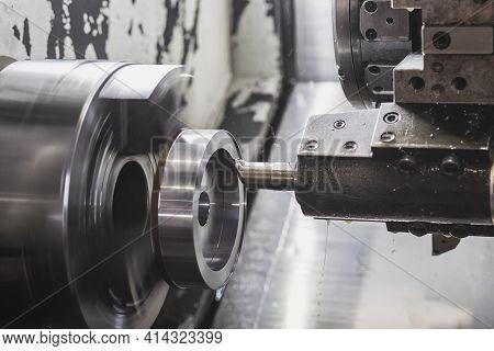A Milling Cutter In A Cnc Machine Cuts A Metal Workpiece That Rotates At High Speed