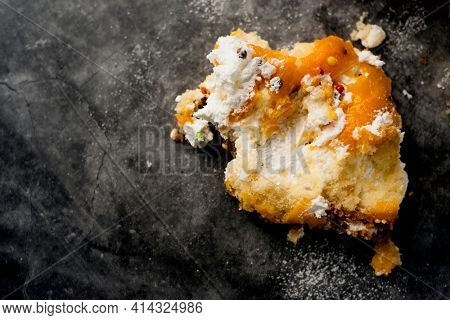 high angle view of the leftovers of a custard cake on a gray stone surface