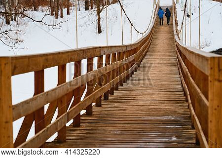 Two Teenagers Walk Together Next To An Old Pedestrian Suspended Wooden Bridge And Light Snow Falls
