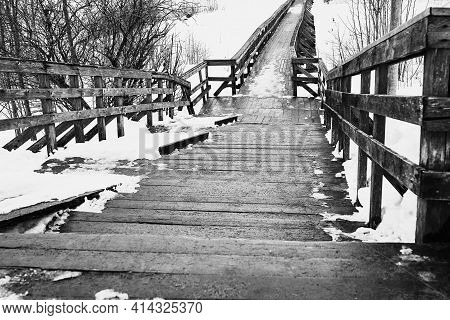 Abstract Empty Old Wooden Bridge Closeup And With Snow In Winter Or Spring On A Black And White Phot