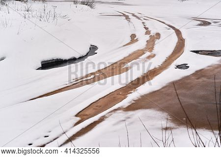 Abstract Spring Landscape Of A Surface Of The River With Car Traces Closeup For A Natural Background