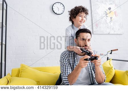 Kyiv, Ukraine - January 15, 2021: Cheerful Arabian Boy Playing Video Game Together With Discouraged