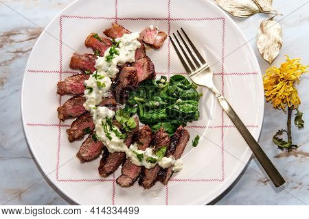 Medium-rare Sirloin Steak With Gorgonzola Sauce And Steamed Spinach