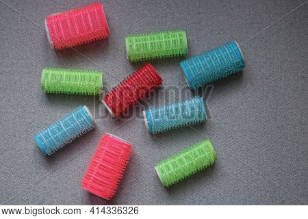 Set Of Colored Plastic Hair Curlers On Gray Table