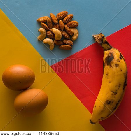 Balanced Diet Food Using Egg,banana And Various Nuts On Plain Three Color Background.