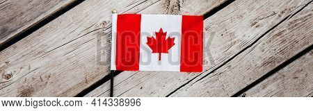 Red Canadian Flag With Red Maple Leaf On Wooden Planks Background Outdoors. Canadian Flag Symbol Dur