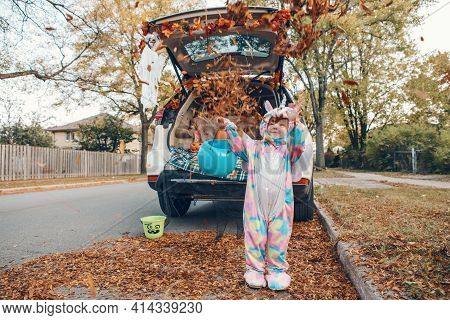 Trick Or Trunk. Happy Baby In Unicorn Costume Throwing Leaves And Celebrating Halloween In Trunk Of