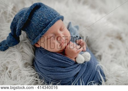 Newborn baby boy sleeps on white fur holding knitted toy in hands. Sweet infant child wearing in blue hat portrait