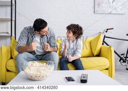Happy Arabian Father Showing Success Gesture While Talking To Cheerful Son.