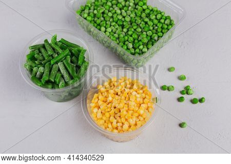 Plastic Container With Different Organic Deep Frozen Vegetables On White Concrete Table. Green Peas,