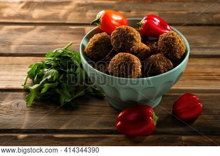 Falafel Balls In A Bowl And Fresh Vegetables On A Wooden Background.falafel Plays An Iconic Role In