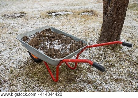 The Garden Wheelbarrow Is Filled With Black Earth. Spring Cleaning The Garden.cart For Carrying Carg