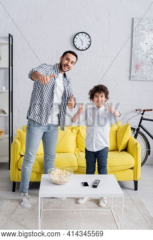 Excited Muslim Father And Son Showing Thumbs Up While Looking At Camera.