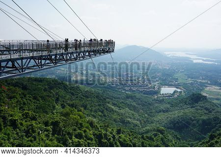 Glass Bridge Platform Over Green Jungle. People On The Bridge Admire The View Of The Mountains, The