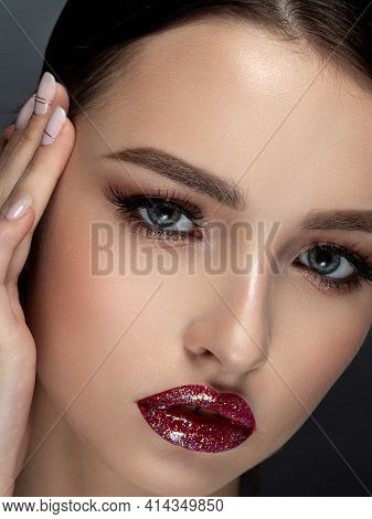 Beauty Portrait Of Young Beautiful Woman With Glittery Red Lips Touching Her Face