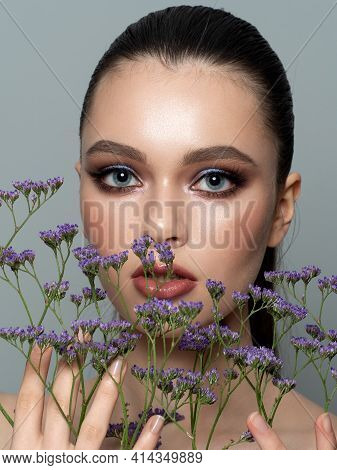 Portrait Of Young Beautiful Woman Holding A Branch Of Violet Flowers