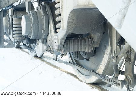 The Wheel Assembly Of An Electric Locomotive Of A Train Standing On Rails Covered With Snow.