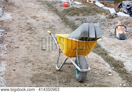 Construction Yellow Wheelbarrow With Loaded Curb Concrete Blocks At A Marked Sidewalk Repair Constru