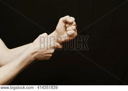 A Hand On A Black Background Is Squeezed Into A Fist And Wants To Commit Violence, Hit Someone, And