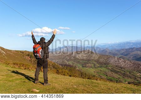 Hiker Raising His Arms At The End Of His Trekking Day. Person Contemplating The Mountains. Weekend G