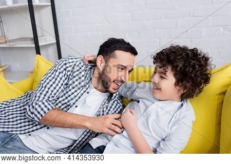 Excited Muslim Man Tickling Happy Son While Having Fun On Sofa.