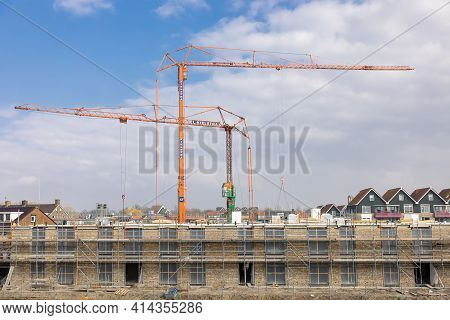 Urk, The Netherlands - March 25, 2021: Big Mobile Tower Cranes At Construction Site Apartment Buildi