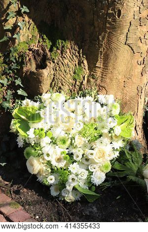Heart Shaped Sympathy Flowers Near A Tree, Various Flowers In Different Shades Of White
